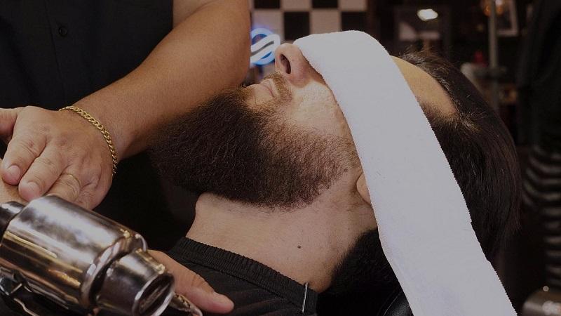 Serviço com toalha quente da barbearia de brasileiros Ultimate Cave em Orlando